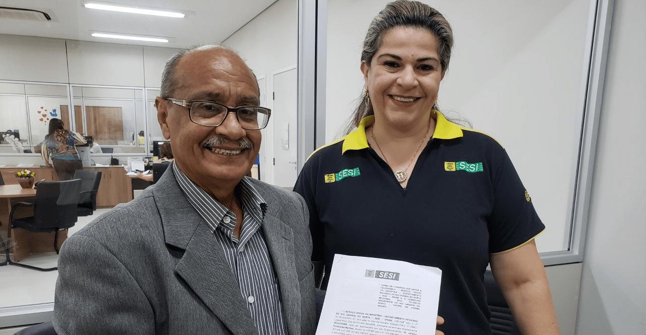 O Presidente do CRT-RN, Jerônimo Andrade, assina acordo com a representante do SESI, a analista administrativa Cristiane Nunes.
